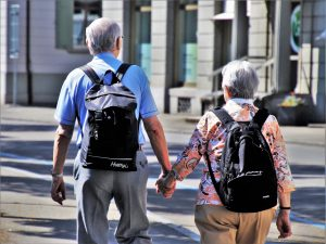 Mature couple with back packs holding hands